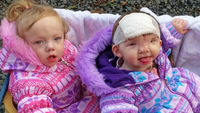 Twins Cora and Violet Pietrok of Stayton take an outdoor ride.