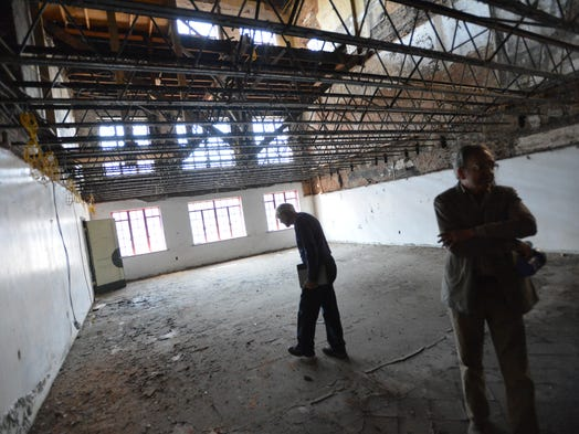 Tom Cook, president for the committee for Staunton Performing Arts Center, and Doug Roller, chairman of the committee for Staunton Performing Arts Center, walk around and explore while giving a tour inside the Arcadia building during an interview in Staunton on Monday, May 19, 2014.
