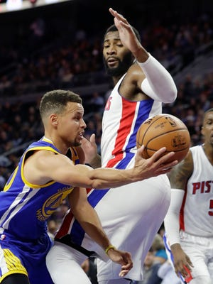 Golden State Warriors guard Stephen Curry passes around Detroit Pistons center Andre Drummond, Friday, Dec. 23, 2016, in Auburn Hills, Mich. The Warriors won 119 to 113.