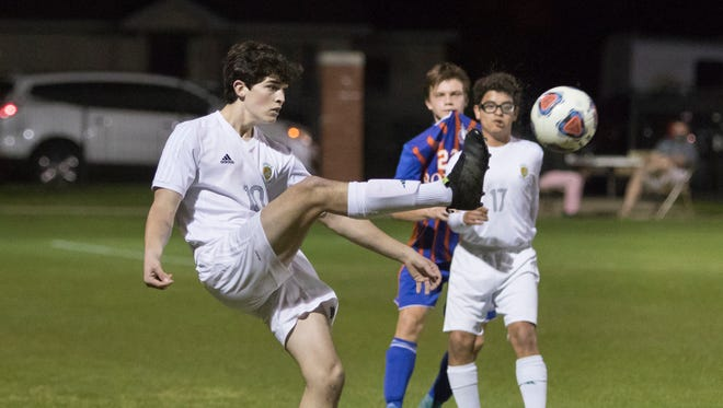 John Carlson (10) kicks the ball up field during the boys regional final soccer match between Pensacola Catholic and Jacksonville Bolles at Pensacola Catholic High School on Wedneday, February 14, 2018.