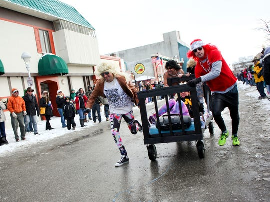 Chris Voss, left, and Bob Emmert of the Bed Rockers compete during the Chilly Fest bed races in downtown Port Huron.