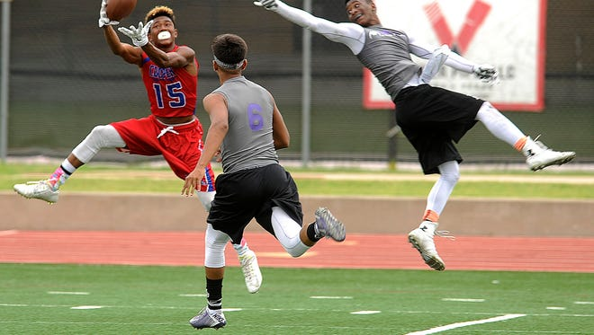 Cooper wide receiver Jwon Hong (15) pulls in a touchdown pass over Fort Worth Paschal defenders during the Abilene 7-on-7 tournament on Friday, June 12, 2015, at Wilford Moore Stadium.