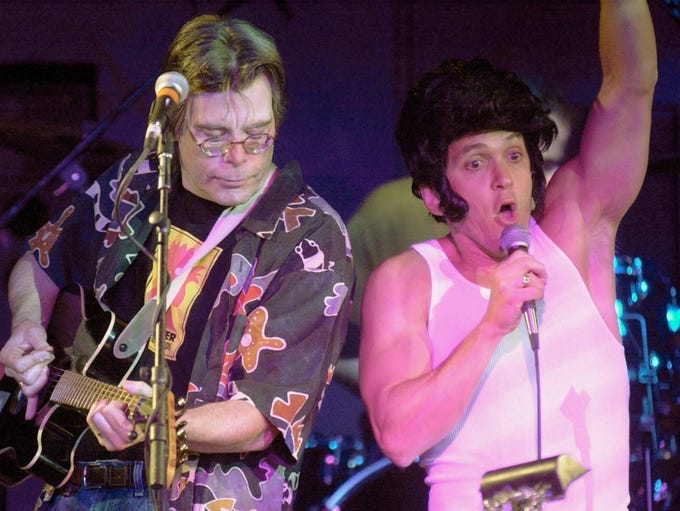 Mitch Albom, right, wearing an Elvis hairdo, sings
