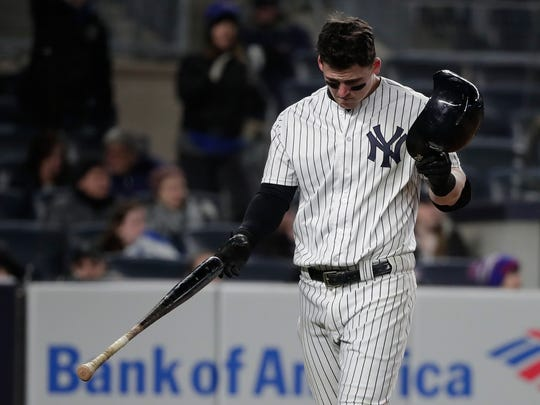 New York Yankees' Tyler Austin pulls off his batting helmet after striking out against the Toronto Blue Jays to end the eighth inning of a baseball game, Friday, April 20, 2018, in New York.