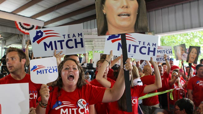 Mitch McConnell supporter Kara Canterbury of Rockcastle County, Ky. yells at Alison Lundergan Grimes supporters as she holds a photo of Grimes at the Fancy Farm picnic Saturday afternoon.  (By Matt Stone, The Courier-Journal) Aug. 3, 2013