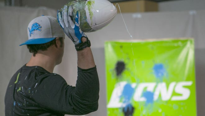 Lions quarterback Matthew Stafford painting a canvas with footballs in a charity effort with REPREVE.