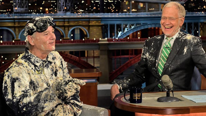 Bill Murray talks with host David Letterman after emerging from a cake to say good-bye Tuesday.