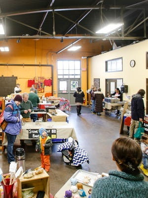 Shoppers peruse booths with fresh, locally grown produce and handmade food and crafts on Wednesday, March 15, 2017, at the Allen Farmers Market on Lansing's east side.