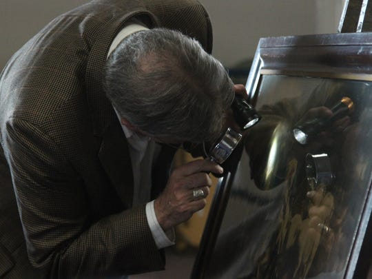 Mark Moran uses a magnifying glass and a flashlight as he examines a print brought in by Howard Bichler of Birnamwood as he appraised items Sunday at the Marathon County Public Library.