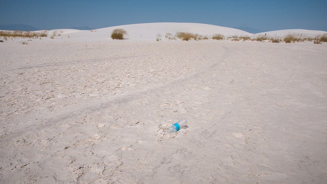 An empty water bottle lies in the gypsum sand at White Sands National Monument in August 2015.