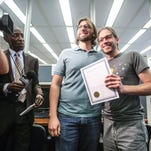 Craig Bowen (left) and Jake Miller hold their certificate of marriage, before becoming the first gay couple married by Marion County on June 25, 2014. Despite being a vocal supporter of same-sex marriage bans in the past, Indiana has remained silent as the U.S. Supreme Court prepares to take up the issue next week.