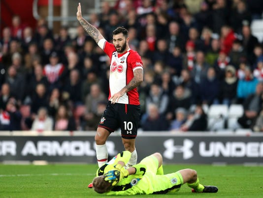 Southampton's Charlie Austin gestures as Huddersfield Town goalkeeper Jonas Lossl lies injured during the English Premier League soccer match between Southampton and Huddersfied at St Mary's, in Southampton, England, Saturday, Dec. 23, 2017. (Adam Davy/PA via AP)