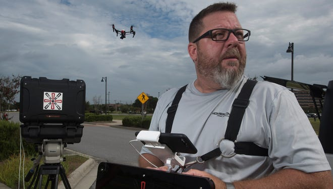 Rick Simpson, president and pilot at Hover Check Drone Imaging, monitors the flight of an unmanned aerial vehicle during a test flight at Community Maritime Park in downtown Pensacola on Wednesday, Aug. 9, 2017.