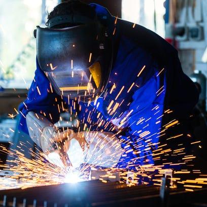 Welder bonding metal with welding device in workshop