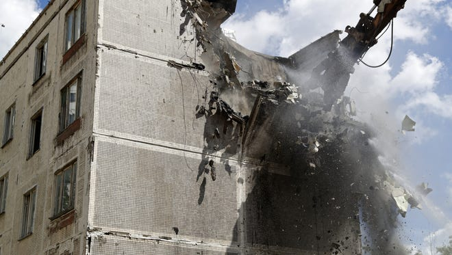 An excavator demolishes a five-story building  in Moscow that was built in the early 1960s, on June 20, 2017. Moscow city authorities initiated a controversial program to demolish Soviet-era apartment blocks.