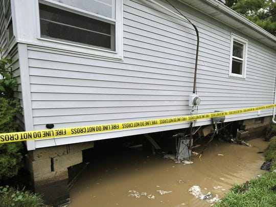 A July 2011 storm caused the collapse of a wall of this home on Burchfield Drive in Lansing. Officials say a new flood plain elevation study could decrease flood insurance rates locally.