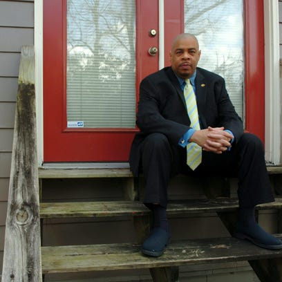 Michael Marks sits on the steps that lead to the back yard of his Hattiesburg home.