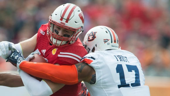 Auburn linebacker Kris Frost  and Auburn defensive back Joe Turner tackles Wisconsin wide receiver Alex Erickson (86) during the Outback Bowl between Auburn and Wisconsin at Raymond James Stadium in Tampa, Fla., on Thursday, Jan. 1, 2015.
