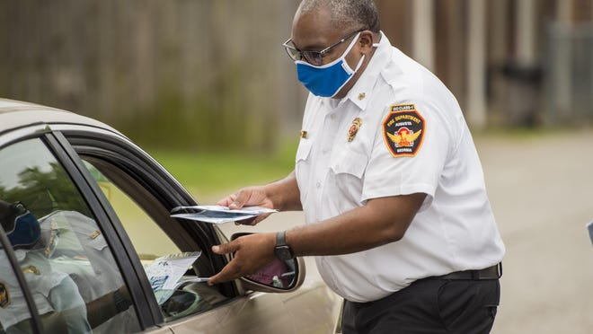 Augusta Fire Chief Chris James hands out free masks during the mask and hand sanitizer giveaway at the Salvation Army Thursday morning August 12, 2020 in Augusta, Ga.