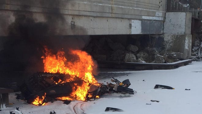 Pictured is the fiery aftermath of a snowmobile that crashed into the Woodland Shore Drive bridge on Woodland Lake Sunday afternoon. The snowmobiler, Robert David Mechigian, died from his injuries.