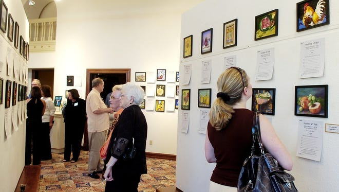 Patrons look at works of art up for auction at the Kemp Center's Mystery Art Fest in 2015.