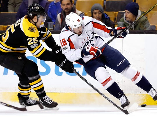 Boston Bruins' Brandon Carlo and Washington Capitals' Chandler Stephenson (18) battle for the puck during the first period of an NHL hockey game in Boston Thursday, Dec. 14, 2017. (AP Photo/Winslow Townson)