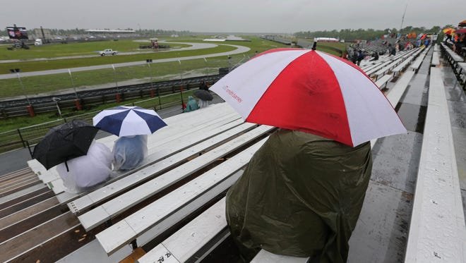 Apr 12, 2015; Avondale, LA, USA; Race fans sit in the rain waiting for IndyCar warm-up prior to the Grand Prix of Louisiana at NOLA Motorsports Park. Mandatory Credit: Chuck Cook-USA TODAY Sports