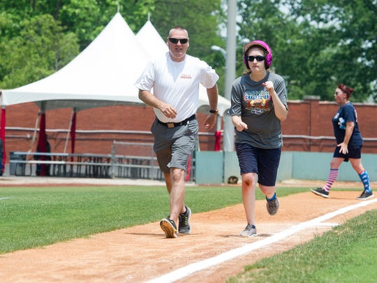 Terry Harmon, left and Maddie Barrett race home during the  Highland Challenger League fundraiser at Bosse Field on June 10, 2018.  Barrett is one of 15 players in the Highland Challenger League who gets to play in an exhibition game during the Little League World Series on August 25 in Williamsport, Pennsylvania.