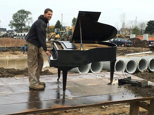 Nico Stante takes a turn on the piano that was found on a new construction site.