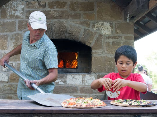 Oven owner Dave Geyer of Oxford lines up pizzas for