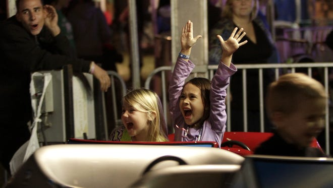 Payton Breadmore, left, and Kelsey Gropp scream as they spin around on the Fast Eddy's Drive In ride at the 2012 St. Andrew Festival in Cape Coral.