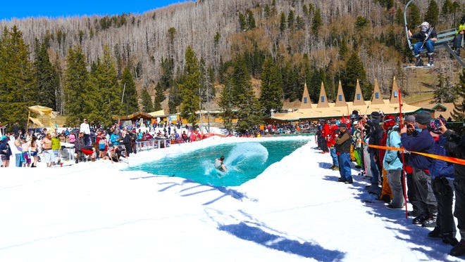 Crowds look on at the annaul Pond Skim contest at Ski Apache Sunday.