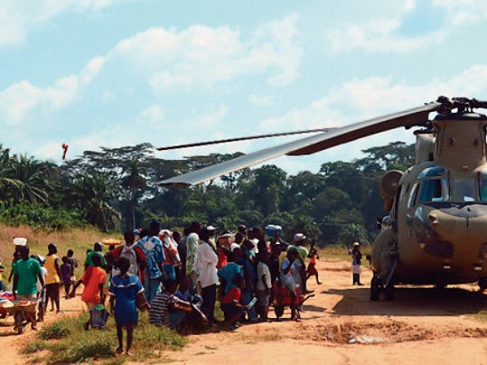 Locals in Ganta, Liberia, observe a CH-47F Chinook helicopter from Task Force Iron Knights, 2nd Battalion, 501st Aviation Regiment, 1st Combat Aviation Brigade, 1st Armored Division, deliver supplies to an Ebola Treatment Unit in support of Operation United Assistance, Dec. 9 2014. Operation United Assistance is a Department of Defense operation in Liberia to provide logistics, training and engineering support to USAID-led efforts to contain the Ebola virus outbreak in western Africa. (U.S. Army photo by Sgt. Jose Ramirez, 1st Combat Avn. Bde., 1st Armored Div. Public Affairs/Released)