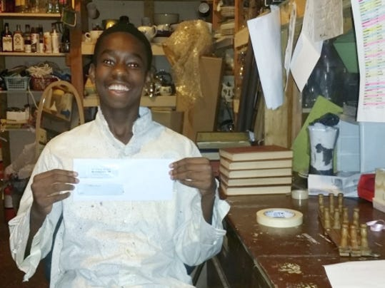 """Terry Berger - Public Opinion LeShan Wilkinson, 14, proudly holds up his paycheck from Totem Pole Playhouse recently while in the theater in Fayetteville. The eighth-grader at Chambersburg Area Middle School plays Gabriel in Totem Pole's musical drama """"Shenandoah!"""""""