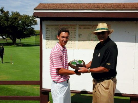 Kevin Crumbling receives his championship plaque from Sherm Keeney after winning the York County Amateur Golf Association Apple Chevrolet Junior Boys' Championship on Monday at Pleasant Valley Golf Club with a 27-hole score of 5-under-par 103.