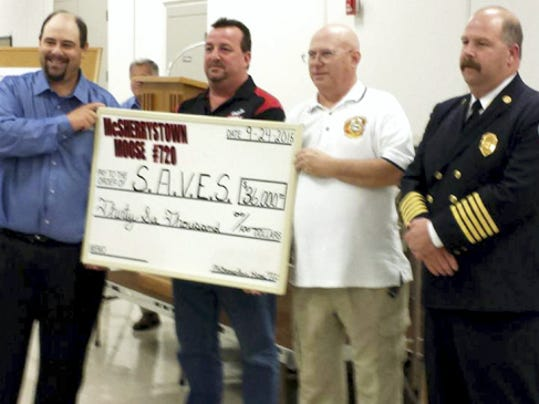"""The Southeastern Adams Volunteer Emergency Services (SAVES) capital campaign kick-off in Conewago Township raised nearly 250,000. Moose Lodge members present their contribution, while Tom Weaver looks on in the background. Pictured holding the check, from left, are: George """"Rookie"""" Chroniger, manager of Moose Lodge 720 in McSherrystown; Shawn Shadle, governor of Lodge 720; President Andrew Weaver, of SAVES; and Chief Thomas Lawrence Jr., of SAVES."""
