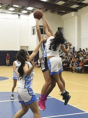 The St. Paul Christian Warriors' Joylyn Pangilinan (14) makes the block on Academy of Our lady of Guam's Mia San Nicolas (2) during their Independent Interscholastic Athletic Association of Guam Girls Basketball League game at St. Paul Christian School gym in Dededo on Nov. 14.