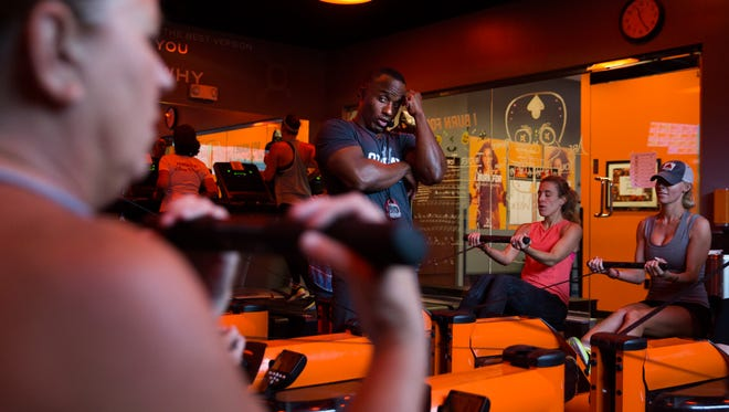 Olaudah Parker encourages participants in a fitness class to keep rowing on Thursday, October 20, 2016 at at Orange Theory Fitness in North Naples. Participants rotate from the rowing machine to the treadmill to weights in the class.