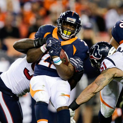 Denver Broncos running back C.J. Anderson (22) is pulled down by Houston Texans defensive end Jadeveon Clowney (90).