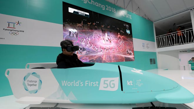 Jaeyoung Too, 52 of Seoul, on a virtual reality bobsled ride as the opening ceremony of the Pyeongchang Olympics is played in the background on a giant TV at Gwanghwamun Square in Seoul.