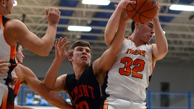 Armada Tigers' Logan Newlands gets a rebound from Almonts' Cade Tank Monday, Mar. 7, during district basketball at Croswell-Lexington High School.