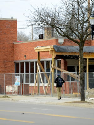A man walks past construction of Arcadia Ales & Smokehouse on March 23, 2017, near the corner of Fairview and Michigan Avenue in Lansing. The brewery will be completed this summer.