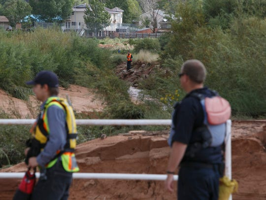 Rescuers search the banks of Short Creek Tuesday, Sep. 15, 2015 looking for five people still missing after flash floods ripped through the twin towns of Hildale and Colorado City Monday.