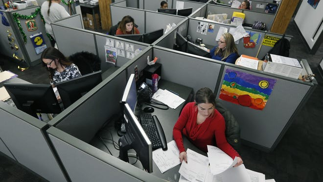 Members of the production team — Renee Fracassi, front right, and behind from left to right is Nicole Horton, Allie Strader and Francine Doran — gather information at Frontier Abstract and Research Services.