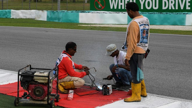 Workers repair a drain cover after Haas F1's Romain Grosjean suffered a hard crash afer hitting the drain during practice Friday for the Malaysian Grand Prix.