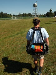 With his bag full of discs, Cooper Rooks makes his way to the first tee of Bainbridge Island's Battle Point Park Disc Golf Course on Wednesday.