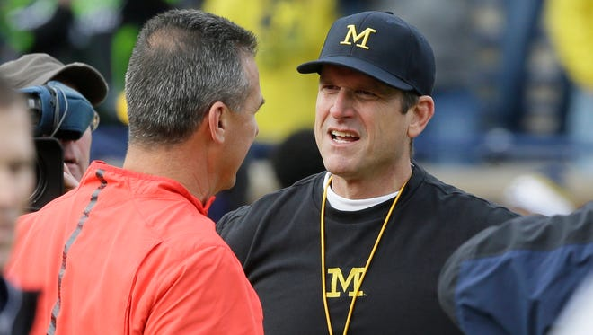 Ohio State coach Urban Meyer, left, meets with Michigan coach Jim Harbaugh before the game on Nov. 28, 2015, in Ann Arbor.