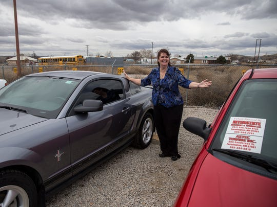 Bloomfield School District Superintendent Kim Mizell shows off a Ford Mustang and Ford Focus on Monday at the district's transportation parking lot.