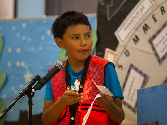 Student Kyrinzo Deele reads a note Friday during a year-end program for Dream DinéCharter School at the Shiprock Chapter House.
