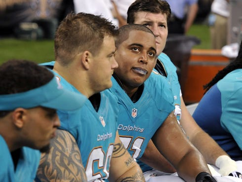 In this Sept. 30, 2013 file photo, Miami Dolphins guard Richie Incognito (68), center left, and  and tackle Jonathan Martin (71), center right, sit on the bench during an NFL game.